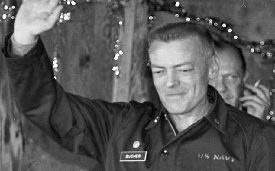A haggard-looking Cmdr. Lloyd Bucher, just released from North Korea after 11 months in captivity, waves as he arrives for a press conference in the NCO Club at the U.S. advance camp near Panmunjom.