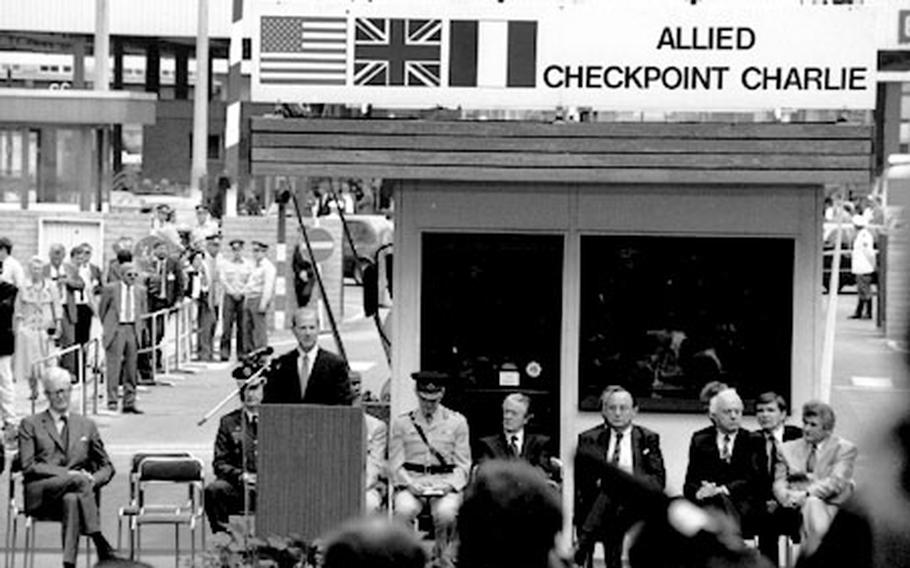 U.S. Secretary of State James A. Baker III speaks at a ceremony marking the closing of Berlin's Checkpoint Charlie in June, 1990
