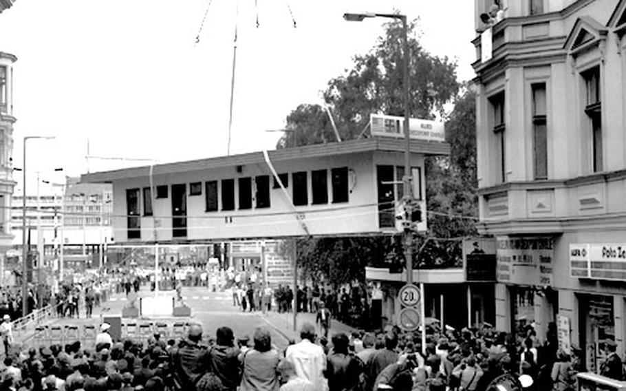 A crane moves the 50-foot-long Checkpoint Charlie guardhouse to a waiting truck after the ceremony.