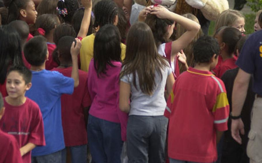 """Daren the Lion, the Drug Abuse Resistance Education mascot, gives high-fives to Kadena Elementary School students after their """"walk away from drugs"""" Thursday."""