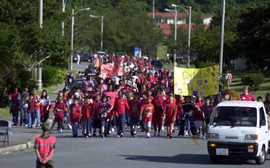"""A wall of students from Kadena Elementary School makes its way through the streets of the housing area surrounding the school during the """"walk away from drugs"""" event Thursday. More than 1,200 students, faculty and parents participated in the walk in celebration of Red Ribbon Week."""