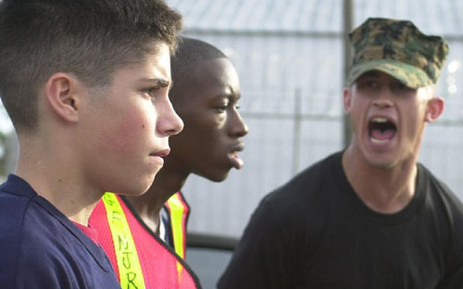 Two Navy Junior Officers' Training Corps cadets receive a tongue lashing from Marine Sgt. Eric Fandrei Thursday at Naval Station Rota, Spain. About 80 high school students from across Europe are in Rota for the NJROTC mini boot camp. Graduation is on Sunday.