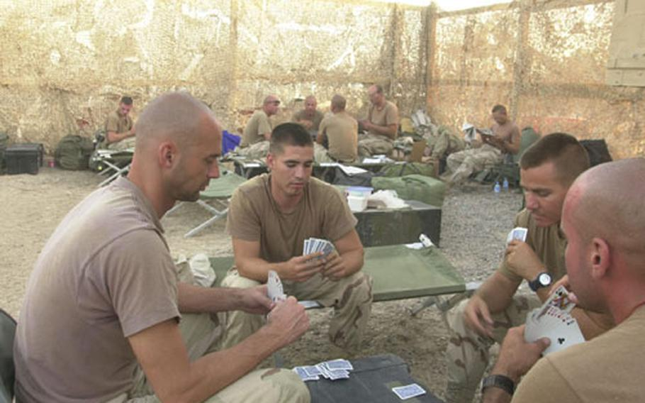 Staff Sgt. Kris Gable, back to camera, waits to play the eight of clubs as Master Sgt. Daniel Gilstrap, left, Sgt. Eduardo Moya, center, and Staff Sgt. Michael Morehead watch the cards going down during a game of hearts. The four noncommissioned officers from the 249th Engineers Battalion in Heidelberg, passed the days waiting to get out of Baghdad International Airport with endless rounds of card games.