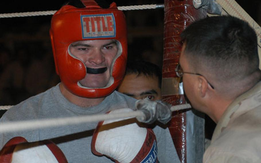 Trainer Spc. Jason Schmidt talks to fighter Spc. Destin Perdue between rounds of their match Friday night. Perdue won a decision against Jared Sell. This was Perdue's first boxing match.