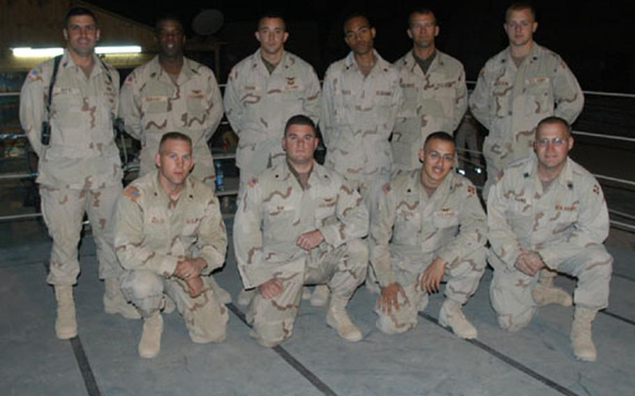 Members of Company A, 404th Aviation Support Brigade, in their homemade boxing ring. They are, back row, from left, Maj. Don Nitti, company commander; 1st Sgt. Gary Durant, who challenged company soldiers to build the ring; Sgt. Jacob Paddon; Spc. Mason Truss; Staff Sgt. Brian Pridemore and Spc. Shawn Jackson. Front row: Spc. Ryan Miller, Spc. Thomas Ray, Spc. Michael Pecero and Spc. Christopher Rains.