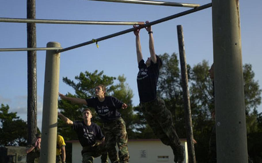 A member of the almost all-female team from the U.S. Naval Hospital Okinawa stretches out to reach the bar on the obstacle course at Camp Schwab Wednesday. The team was comprised of only females until Tuesday, when one team member injured her ankle and a male alternate took her place.