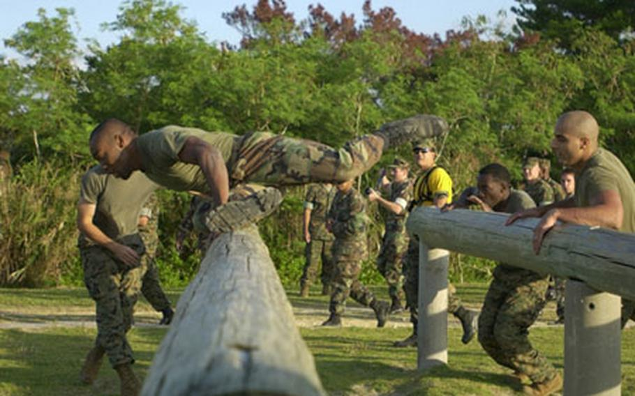 Members of the 1st Marine Air Wing team make their way over the logs at Camp Schwab's obstacle course Wednesday during the Battle Skills Competition.