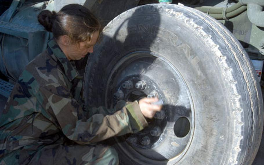 Spc. Lee Anne Truesdell of the 705th Transportation Company (POL), an Army Reserve unit from Ohio, tightens bolts on a tire at LSA Anaconda, Iraq. Maintenance has been a big reason for the company's success in Iraq.