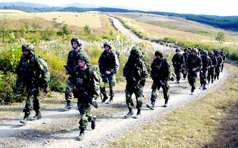 Soldiers march through the hills where members of Hawaii's Alpha Company of the 2nd Battalion, 27th Infantry, 25th Infantry Division trained Friday with Japan Ground Self-Defense Force troops.