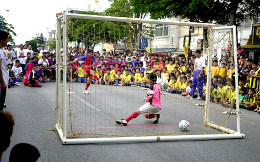 Hundreds look on as a goal is scored during a soccer competition at the Okinawa International Carnival in Okinawa City Saturday. Kids also were able to compete in a three-on-three basketball tournament.