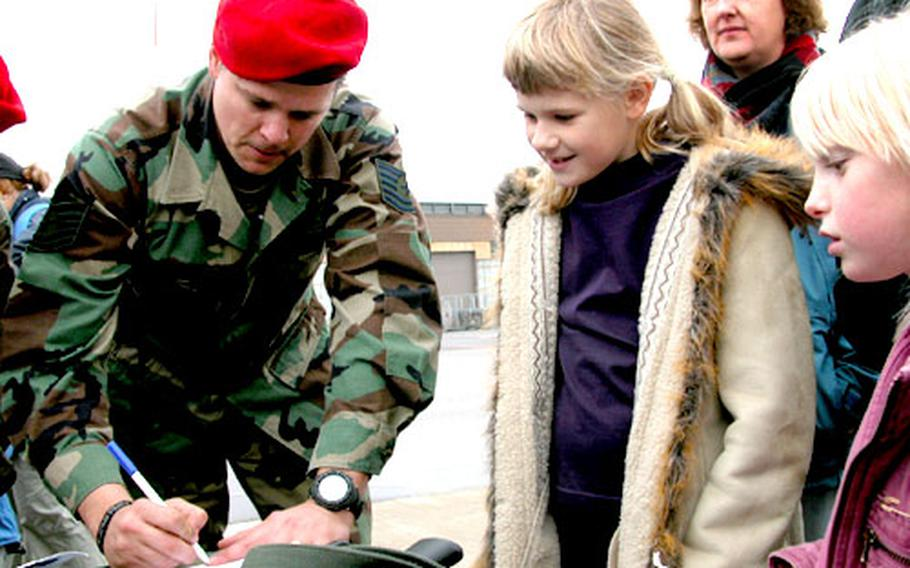 Tech. Sgt. Ty Clark from RAF Mildenhall signs an autograph Friday during Sibling Appreciation Day, which was to entertain the brothers and sisters of terminally ill children.
