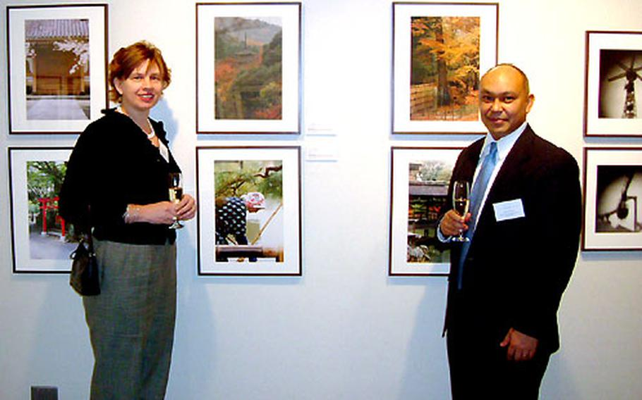 """Lt. Col. Tony Plana and his wife, Brenda, stand in front of some of their photographs on display in Tokyo. The photos are featured as part of an exhibit on """"Japan through Diplomats' Eyes."""""""