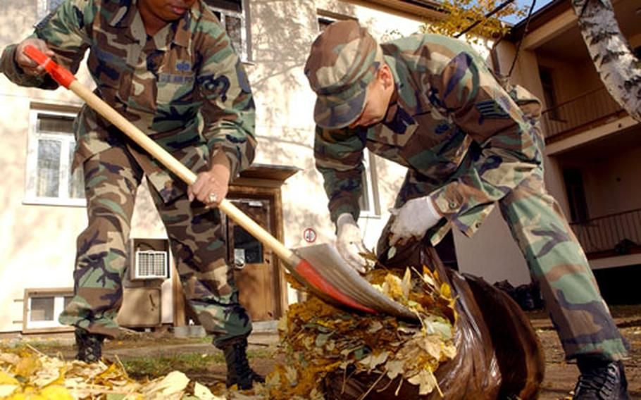 Master Sgt. Beverly Dennie, left, and Staff Sgt. Mark Cave gather up leaves Tuesday at Rhein-Main Air Base, Germany, during Fall Clean Up, part of USAFE's Combat Proud Program. Everyone from the lowest ranking airman to the base commander got in on the act, as airmen from the base policed up the areas around their squadrons. They also will clean up the family housing area Thursday.