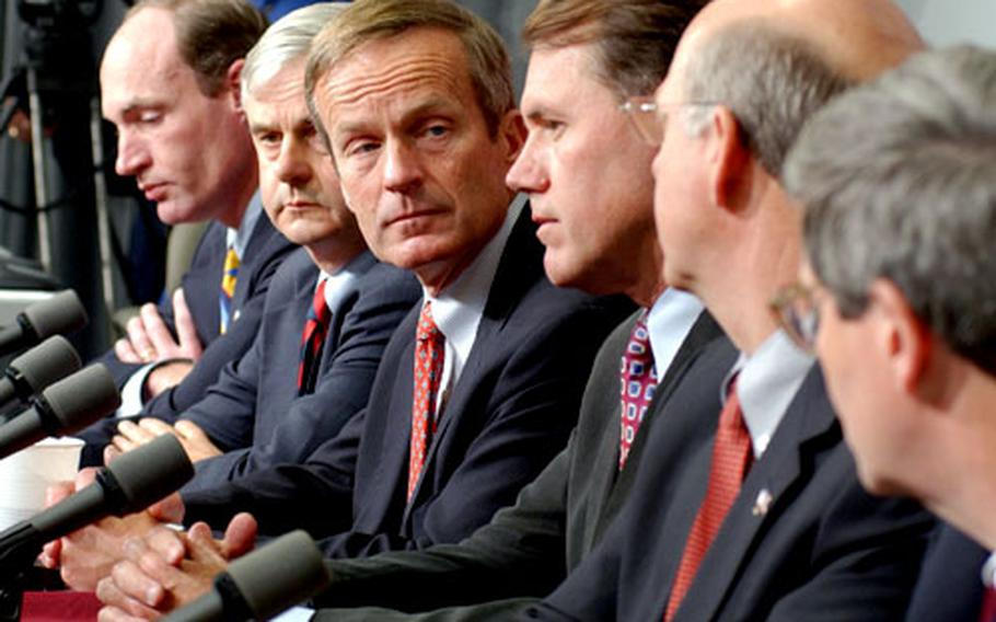 Left to right: Reps. Thaddeus McCotter, R-Mich.; Jeb Bradley R-N.H.; Todd Akin, R-Mo.; Ed Case, D-Hawaii; and Steve Pearce, R-N.M., listen to Brad Miller, D-N.C., discuss their visit to Iraq during a news conference at the Landstuhl Regional Medical Center on Tuesday. The congressmen visited wounded servicemembers there following their return from Iraq.