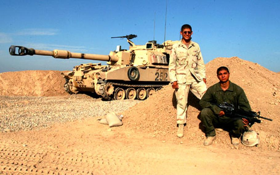 """Brothers Staff Sgt. Enrique Decal, left, and Spc. John David Zapata are in the same 3rd Battalion, 16th Field Artillery unit, platoon at Camp Warhorse, Iraq, a few hundred yards away from the South Dakota National Guard's 200th Engineer Company. Decal is a Howitzer section chief with one M109A6 Paladin 155mm self-propelled artillery piece and Zapata is a ammo team chief with another gun in the """"Redlegs"""" platoon."""