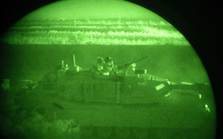 A soldier in an Abrams tank scans outside the Camp Warhorse, Iraq, perimeter after the base was mortared Sunday night. Artillery was fired toward the suspected mortar launch sites, and tanks and helicopters headed to the area minutes later. This photo was taken through a night-vision monocle.