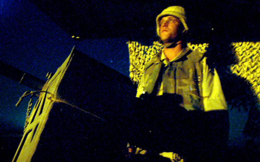 Spc. Chad Larson watches the countryside outside Camp Warhorse's north gate Sunday night after the base was attacked with mortars. Larson has his M-16 rifle and Mk-19 40mm grenade launcher with him in the second-story tower.