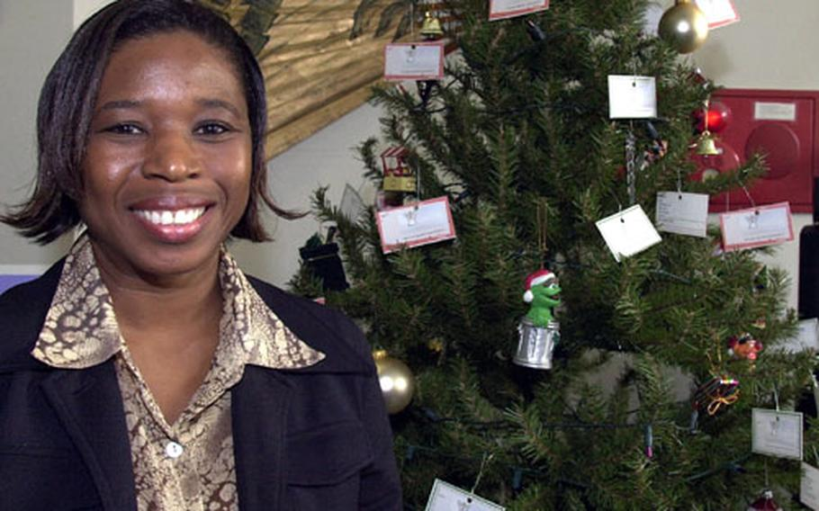"""Barbara Lucy, Family Support Center family services coordinator, stands next to the holiday """"Angel Tree"""" in the center's lobby at Yokota Air Base. Community members may turn in children's names for the Angel Tree Program through Nov. 21."""