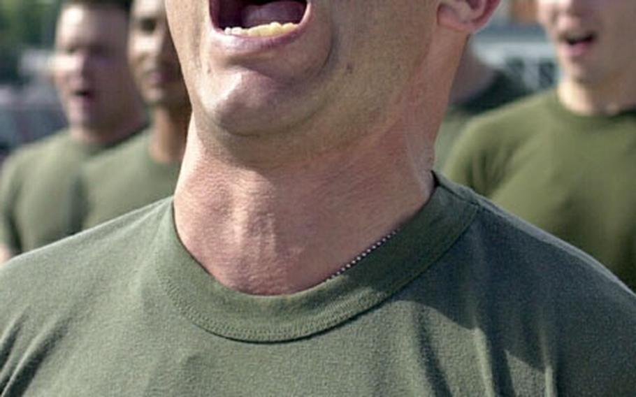 """Marine Gunnery Sgt. Juan Lizalde screams after singing the """"Marine Hymn"""" Friday at Naval Statioin Rota, Spain. Lizalde and about 200 members of Marine Corps Security Force Company, Europe, sang the hymn before running the last leg of a 228-mile company run in celebration of the Marine Corps' 228th birthday. The Marine ran the 228 miles in shifts, beginning on Wednesday."""