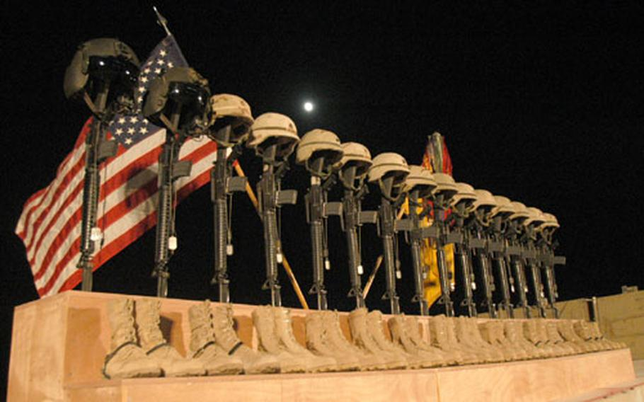 Fifteen sets of helmets, rifles, dog tags and boots were placed in front of a U.S. and Army flag as a memorial to the 15 soldiers killed in the downing of a Chinook helicopter Sunday. Hundreds of soldiers and civilians attended the memorial service Thursday night at the Rifle Base stadium on al-Asad Air Base, Iraq.