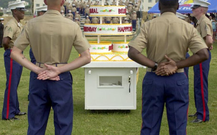 Master Gunnery Sgt. Octavio Smith, right, and Pfc. Derek Richardson, left, the oldest and youngest Marine, stand in front of the Marine Corps Birthday cake during the uniform pageant and cake cutting ceremony on Camp Foster Friday. Smith was born March 15, 1948 and Richardson on Oct. 16, 1985.