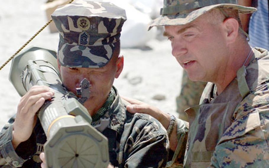 Marine 1st Sgt. Ron Dickenson, right, explains the procedures of a shoulder-fired anti-armor weapon to a Philippine Marine scout during the Talon Vision exercise in central Luzon.