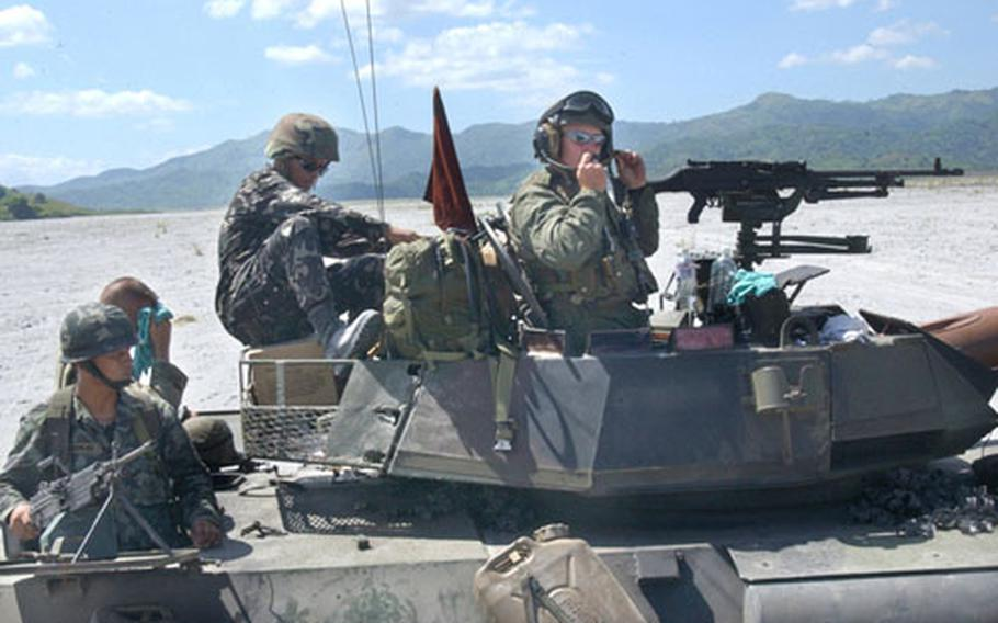 A Philippine Army scout team rides in the rear of a U.S. Light Armored Vehicle during a live-fire exercise during the Talon Vision exercise in central Luzon.
