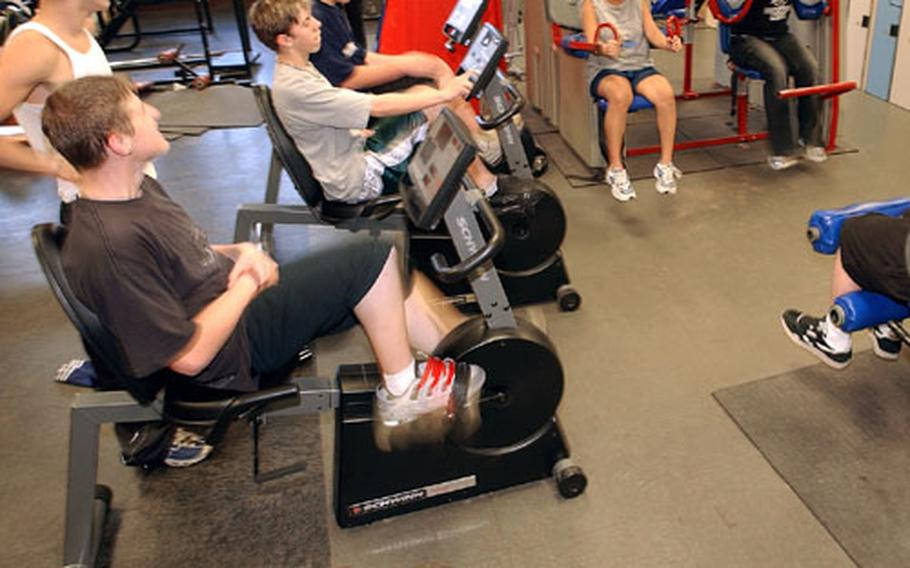 Students at Ramstein High School in Germany work out on exercise bikes and other fitness machines during a recent gym class.