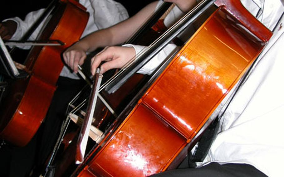From left, Dexter Simpson, Mary Beth Brown and Taylor Hollen play their cellos Tuesday during a performance by London Central High School musicians at Liberty Elementary School on RAF Lakenheath.