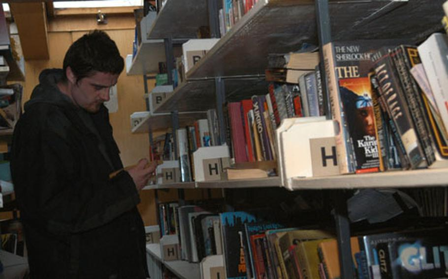 A Bosnian reader checks out books on shelves of the American library, a part of the National University Library in Tuzla, Bosnia and Herzegovina. A joint project of the U.S. Embassy in Bosnia and Herzegovina and U.S. troops serving with Stabilization Force will introduce a state-of-the-art library area replacing the cramped section where the American library is now.