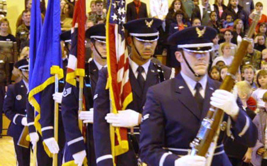 The Liberty Wing Ambassadors in Blue Honor Guard from RAF Lakenheath, England, carries the U.S. and British flags across the floor of the gymnasium at Lakenheath Elementay School during a ceremony Monday in honor of British Remembrance Day and U.S. Veterans Day.