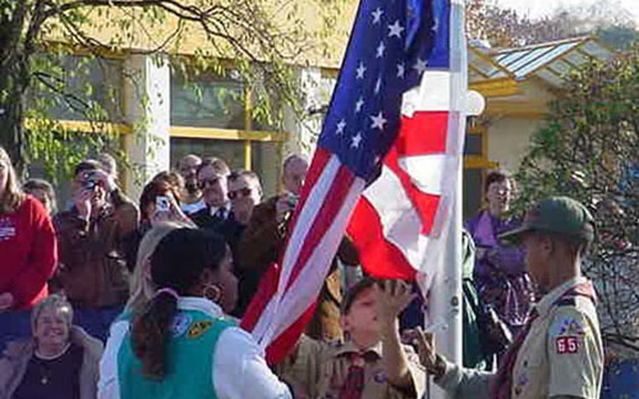 Cub Scouts and Girl Scouts help raise the U.S. flag as Darmstadt Elementary School, Germany, dedicates its new flag pole during a Veterans Day ceremony Monday at the school. The scouts are (from left) Maya Gordon, Rochelle Gardner, Jimmy Czech and Jazz Jackson.