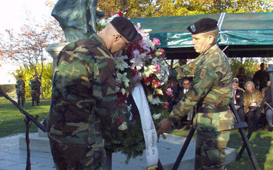 """Spc. Billy Barnes (left) and Maj. Gen. John Batiste, the 1st Infantry Division commander, lay a wreath in honor of 1st ID soldiers awarded the Medal of Honor for heroism. Barnes, 26, of the 1st Battalion, 63rd Armor Regiment, earned a Purple Heart and an Army Commendation Medal with a """"V"""" device for valor after being shot during a firefight May 18 near Al Hawija, Iraq."""