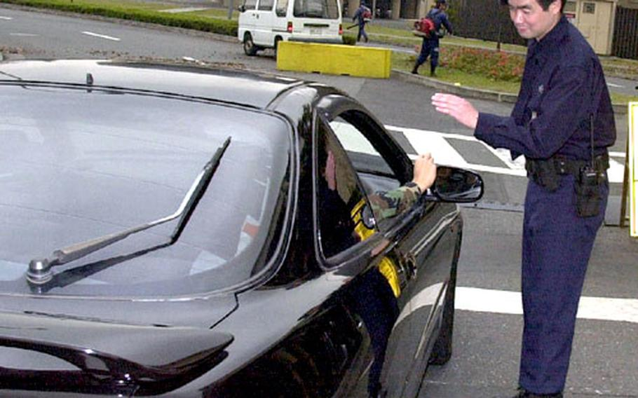 A civilian guard does a spot check for seat belt use at Yokota Air Base, Japan.