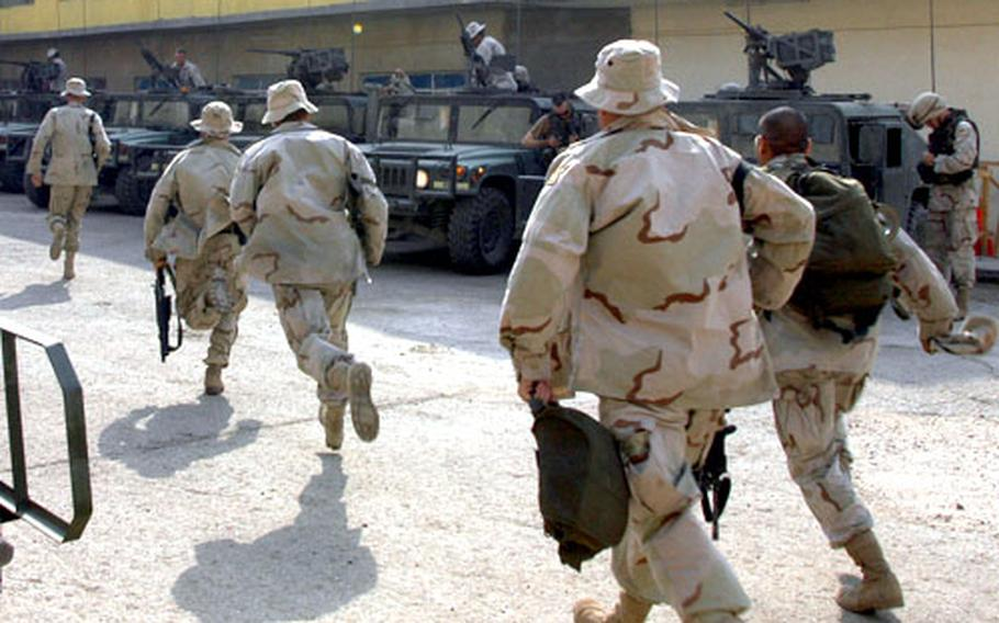 Members of the 1st Armored Division's 1st Battalion, 36th Infantry Regiment race to their Humvees after an explosion is heard outside the battalion's compound in Baghdad Tuesday morning. The troops, members of a scout platoon, serve as a quick-reaction force for such incidents. The explosion turned out to be demolition troops blowing up a mortar round that had been fired into the outlying neighborhood on an earlier occasion.