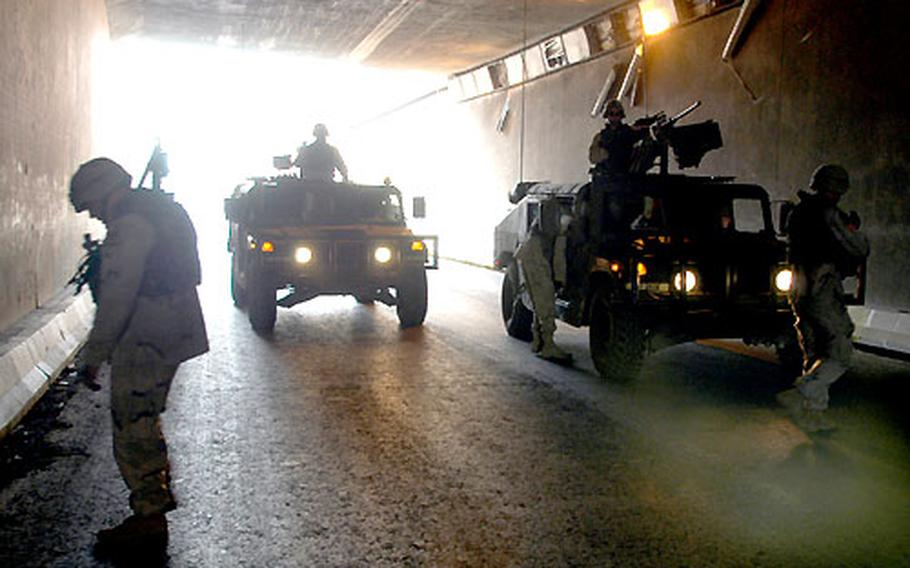 Members of a quick-reaction force from 1st Armored Division's 1st Battalion, 36th Infantry Regiment, look over blast damage inside an underpass in a crowded section of Baghdad Tuesday. Troops drove to scene after a report of an explosion, but could not immediately determine when the blast occurred. There were no reported injuries.