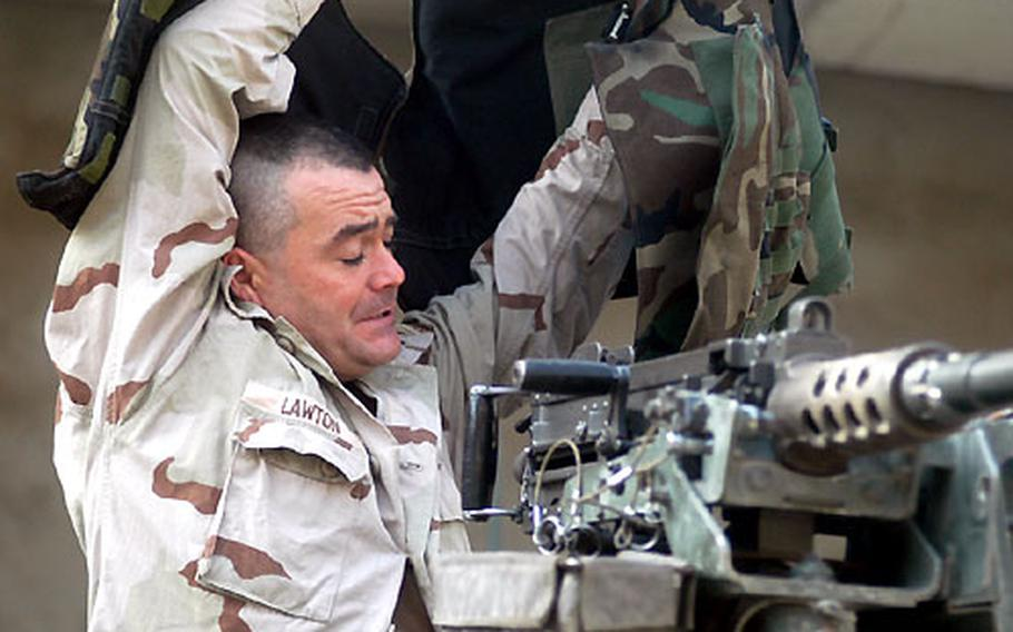 Spc. John Lawton rushes Tuesday to put on his flak vest Tuesday before racing out of Firebase Melody in Baghdad to investigate an explosion near the base. The scouts of 1st Battalion, 36th Infantry Regiment are ready in a moment's notice to respond to reports of trouble.