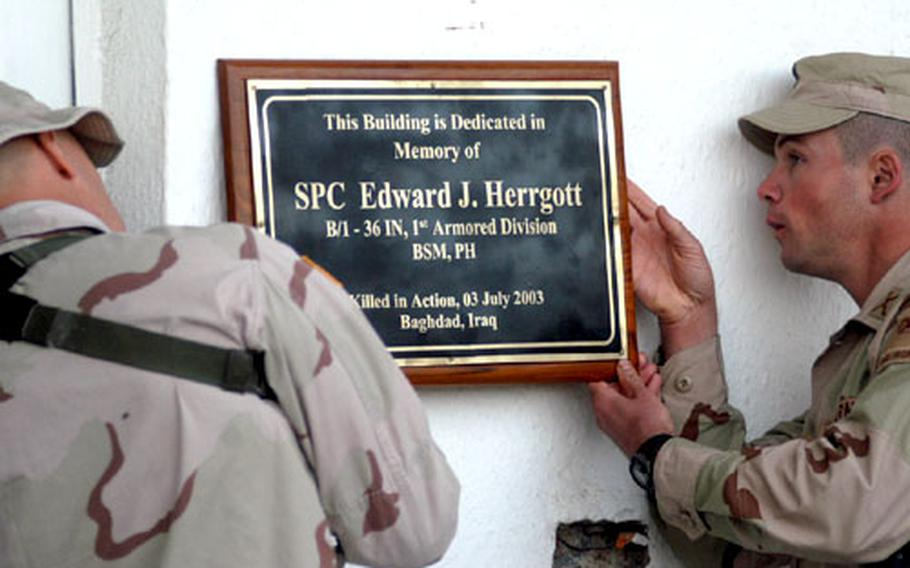 Lt. Col. Chuck Sexton, left, commander of 1st Battalion, 36th Infantry Regiment, part of the 1st Armored Division, and Capt. Chris Ayers, commander of Company B, honor one of their fallen soldiers Tuesday by placing a plaque on a building at their camp in Baghdad.