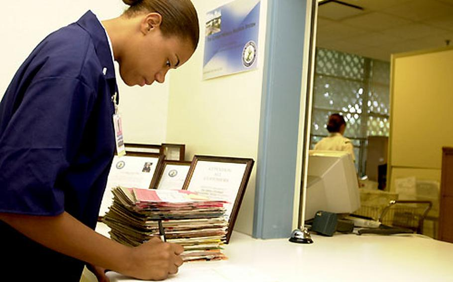 Seaman Apprentice Denise Robinson, a pediatric corpsman, checks out medical records Monday for people with Tuesday appointments at the U.S. Naval Hospital Okinawa.