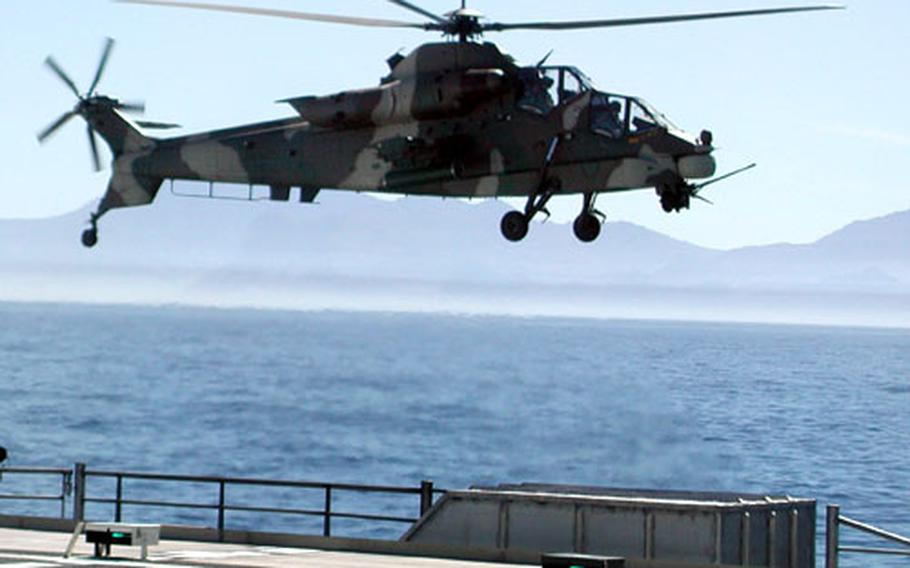 A South Africa Air Force Rooivalk attack helicopter escorts the ship during flight operations. South African pilots in the Oryx maritime helicopter conducted several landings and launches from High Speed Vessel Swift's flight deck as part of West African Training Cruise 2004.