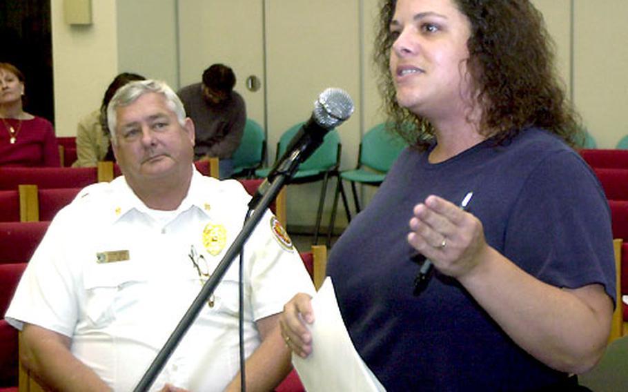 Hario Housing Village resident Peggy Hylton asks questions as Fire Chief Scott Rhode listens.