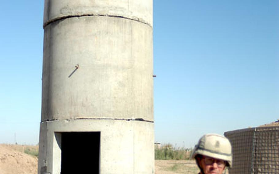 Sgt. Maj. Daniel Ous of 1st Battalion, 8th Infantry Regiment, 3rd Brigade Combat Team, part of the 4th Infantry Division, shows off a prototype for a guard tower developed at FOB Eagle. The towers are supposed to less vulnerable to attacks by rocket-propelled grenades, which in some cases would glance off the tower. The camp will soon have nine of the locally made towers placed on the perimeter.