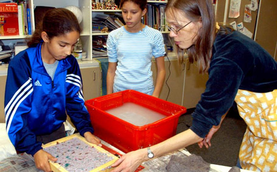 Eljalill Spazier, right, a Heidelberg city worker, helps Kahra Kelty, left, and Krizia Apont to make sheets of paper Thursday at Patrick Henry Village.