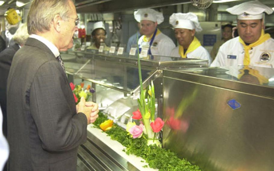 Defense Secretary Donald Rumsfeld getting his lunch of salmon and vegetables onboard USS Blue Ridge.