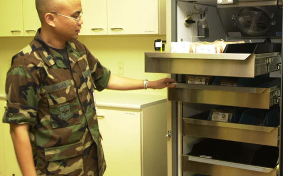 Air Force 1st Lt. Jerome Vinluan, the assistant director of the Armed Services Blood Bank Center, displays the center's stock of units of blood. As of Friday, the center had 102 units on hand. They're supposed to always stock at least 150.