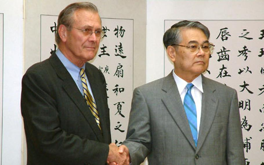 U.S. Secretary of State Donald Rumsfeld and Okinawa Gov. Keiichi Inamine shake hands for the cameras during their brief meeting Sunday in Naha. Inamine gave Rumsfeld a petition requesting the reduction in the number of American troops and bases on Okinawa.