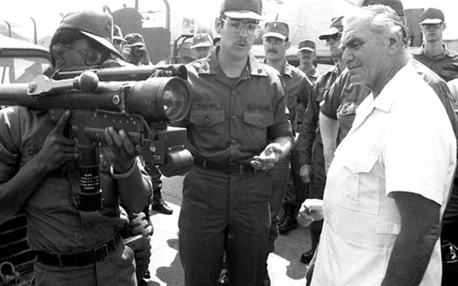 Ernest Borgnine learns about the Redeye missile launcher from Spec. 4 Eddie Chew, left, and Cpl. James Nangano of the 4th Battalion, 69th Armor.
