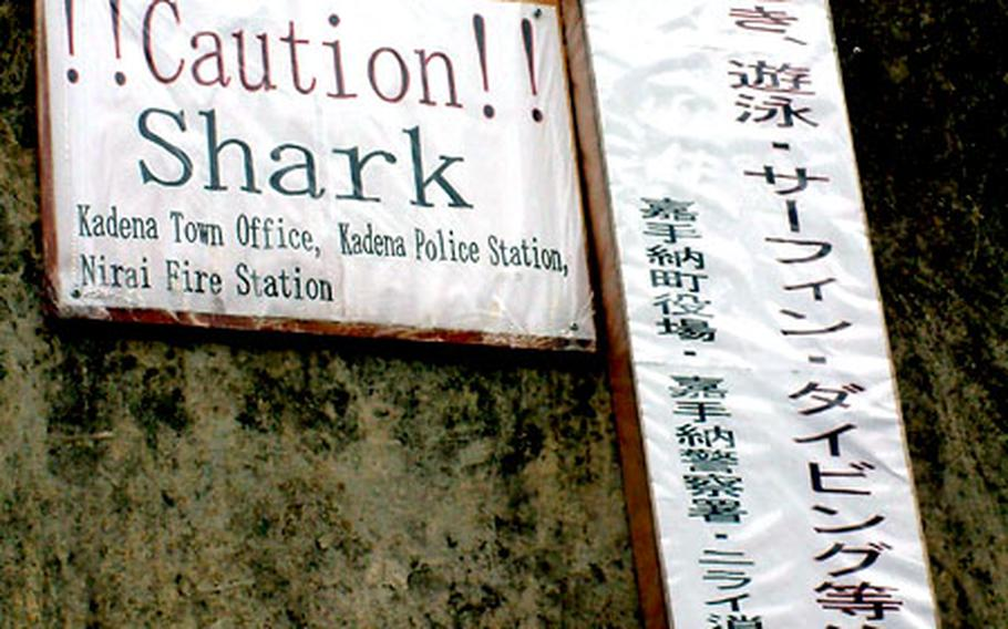 Signs in English and Japanese warn people to be careful in a coastal area of Okinawa where a shark was sighted last month.