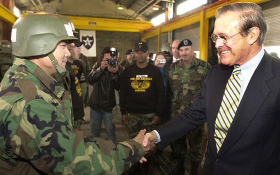 Secretary of Defense Donald Rumsfeld greets a member of the 2nd Infantry Division at Camp Casey, South Korea, on Tuesday. The soldiers were taking part in Air Assault qualifications.