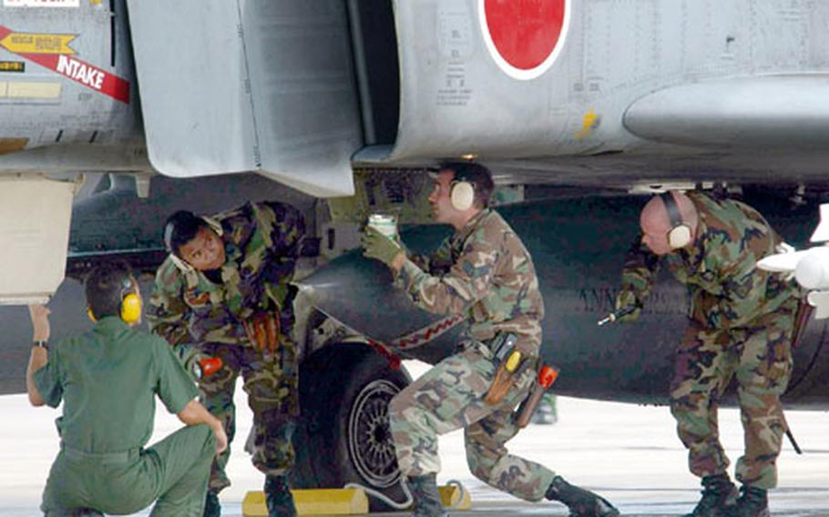 U.S. and Japanese military personnel conduct a familiarization training on a Japan Air Self-Defense Force F-4 aircraft at Andersen Air Force Base, Guam, during exercise Cope North 04.